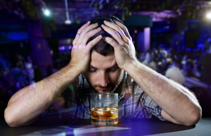 young drunk man in casual shirt depressed and wasted with hands on his head drinking a glass of whiskey at evening disco nightclub feeling dejected and overwhelmed by problems at work or at home