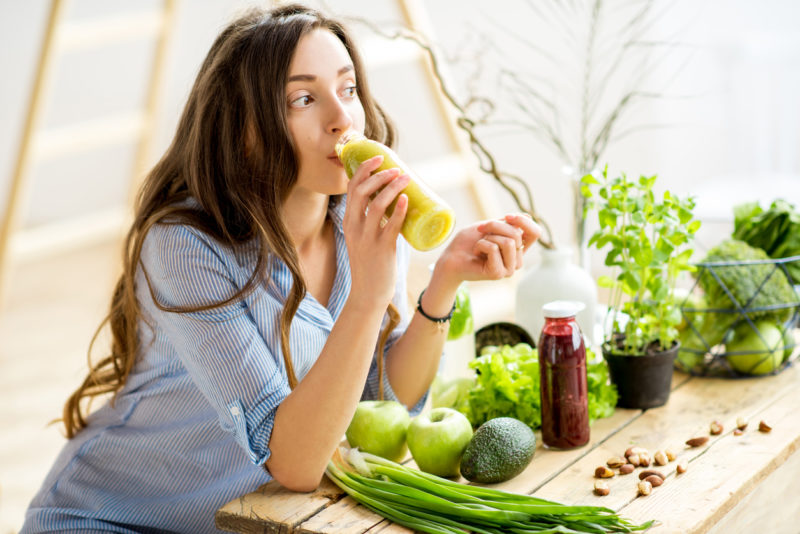 Beautiful woman sitting with healthy green food and drinking smoothie at home. Liver and Kidney detox concept