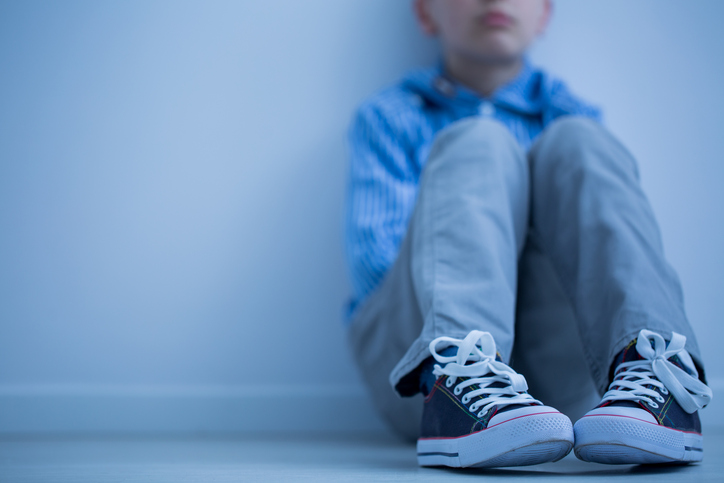 Sad boy in sneakers with alcoholic parents sits in his room alone.