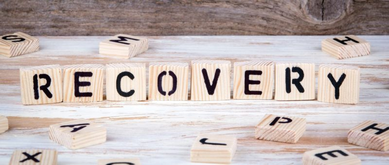 Recovery spelt out in wooden letters on a wooden background. Concept of how to make someone stop drinking alcohol